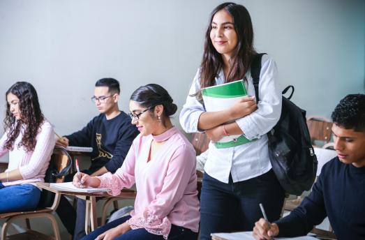 Une étudiante avec des livres debout dans une salle de classe